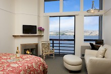 Bayview Suite - comfy couch with ottoman, king bed, roaring fireplace, private balcony and stunning view of Tomales Bay and Rolling Hills gallery image